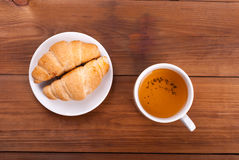 Cup of tea and croissants Stock Images