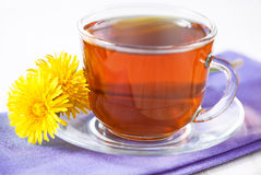 Cup of tea and dandelions Stock Images