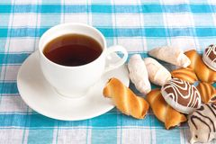 Cup of tea and delicious cookies on checkered tablecloth Stock Photos
