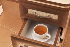 Cup of tea in desk drawer. Cup of tea in open desk  drawer Royalty Free Stock Photo