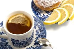 The cup of tea, donut and lemon. There is a cup of tea and donut isolated on the white background Stock Photo