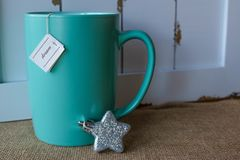 Cup of tea with a dream tag and star ornament. Turquoise mug of hot  tea with a dream tag and a glittery star ornament against a rustic background of wood and Royalty Free Stock Photography