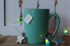 Cup of tea with a dream tag, star ornaments, and lights. Turquoise mug of hot  tea with a dream tag and a glittery star ornaments against a rustic background of Royalty Free Stock Photos
