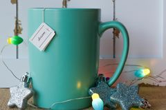 Cup of tea with a dream tag, star ornaments, and lights. Turquoise mug of hot  tea with a dream tag and a glittery star ornaments against a rustic background of Stock Photo