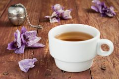 Cup of tea and dried leaves of orchids royalty free stock photography