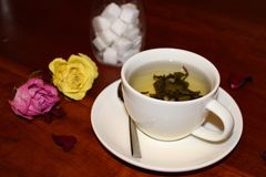 Cup of tea with dried rose buds stock photos