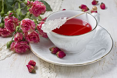 Cup of tea with dried rose buds and fresh roses Stock Images