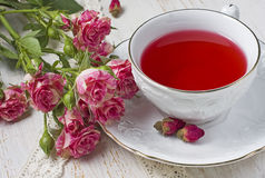 Cup of tea with dried rose buds and fresh roses Royalty Free Stock Image