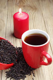 Cup of tea and dry black tea and candle Royalty Free Stock Photos