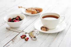 Cup of tea with dry rose buds Stock Photo