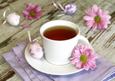 cup of tea, easter eggs and chrysanthemums on old Stock Images