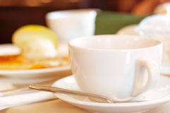 Cup of tea. Elegant white cup of tea on a table in a restaurant. Table covered with beige cloth. On the table dishes: plates with dessert, metal devices, green Royalty Free Stock Image