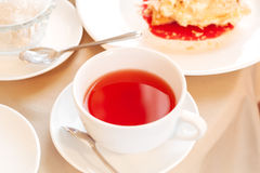 Cup of tea. Elegant white cup of tea on a table in a restaurant. Table covered with beige cloth. On the table dishes: plates with dessert, metal devices Stock Images