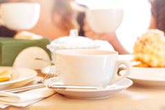 Cup of tea. Elegant white cup of tea on a table in a restaurant. Table covered with beige cloth. On the table dishes: plates with dessert,  sugar bowl, metal Royalty Free Stock Image