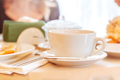Cup of tea. Elegant white cup of tea on a table in a restaurant. Table covered with beige cloth. On the table dishes: plates with dessert, sugar bowl, metal Stock Photography