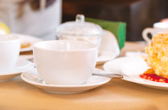 Cup of tea. Elegant white cup of tea on a table in a restaurant. Table covered with beige cloth. On the table dishes: plates with dessert,  sugar bowl, metal Royalty Free Stock Photography