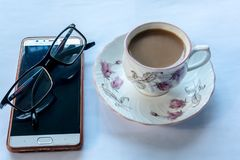 Cup of tea with eyeglasses and smart phone on isolated white background. Close up and Side angle view royalty free stock image
