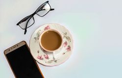 Cup of tea and eyeglasses, smart-phone on white isolated background. royalty free stock images