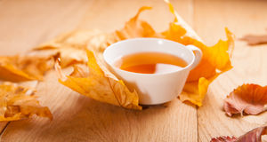 A cup of tea with falling autumn leaves of maple, on the background of the wood table. A still life with a cup of tea with falling autumn leaves of maple, on the stock image