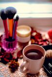 Cup of tea and female accesories on the table. Sweets cosmetics candle rose petals. Female concept stock image