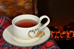 A cup of tea by the fireplace. In a cold winter night Stock Photos