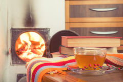 Cup of tea and flames of fire in a fireplace Royalty Free Stock Photos