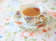 Cup of tea on flower print fabric Royalty Free Stock Image