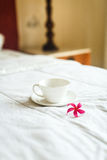 Cup of tea and flower on white bed Royalty Free Stock Photography