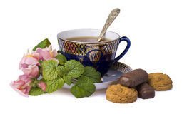 Cup of tea with flowers. And crackers royalty free stock photography