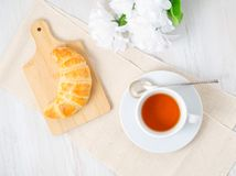 Cup of tea, flowers and fresh baked puff pastry on a white table. Delicious croissants on wooden board, top view royalty free stock photo
