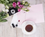 Cup of tea, flowers, vintage camera, earphones, lipstick and she Royalty Free Stock Images