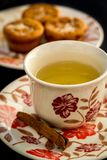 Tea with muffins. A cup of tea in the foreground and a plate with muffins in a blurry background Stock Image