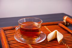 Cup of tea with fortune cookie in oriental style on a wooden background stock photo