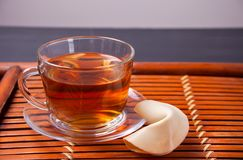 Cup of tea with fortune cookie in oriental style on a wooden background royalty free stock photo