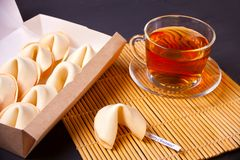 Cup of tea with fortune cookies, teapot in oriental style on a wooden background royalty free stock photo