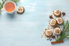 A cup of tea with fragrant honey Christmas gingerbreads with glaze and nuts. With Christmas tree branches and spices on a light blue background, free space stock images