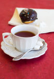 A cup of tea with fresh chocolate donut. A cup of tea with fresh chocolate sufgniya (donut Royalty Free Stock Photography