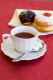 A cup of tea with fresh chocolate donuts. A cup of tea with fresh chocolate sufgniyot (donuts Royalty Free Stock Images