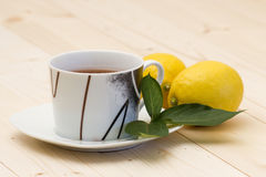 Cup of tea and fresh lemons Stock Photos