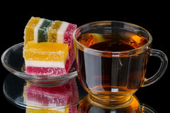 Cup of tea with fruit candy on black Stock Photography