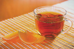 Cup of tea and fruit jelly on a bamboo table cloth Royalty Free Stock Images