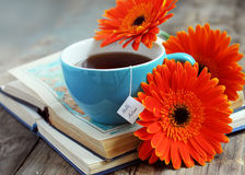 A cup of tea with gerbera flowers and books Royalty Free Stock Images