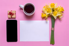 A cup with tea, a gift, a piece of paper, mobile and a bouquet of daffodils Royalty Free Stock Photo