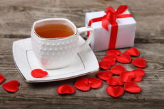 Cup of tea, gift and red hearts Stock Images