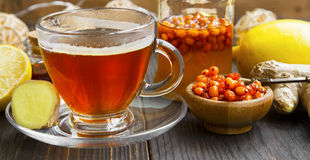 Cup of tea with ginger, honey,seabuckthorn and lemon .Winter col Royalty Free Stock Photos