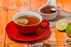 Cup of  tea with ginger,   raspberry jam and lemon Stock Image