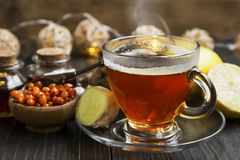 Cup of tea with ginger, seabuckthorn and lemon .Winter cold reme Stock Photos