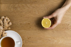Cup of tea and ginger on wooden background. Hand of woman with lemon. Top view. Stock Photos