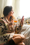 Cup of tea the girl with the phone Royalty Free Stock Images
