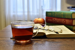 Cup of tea, glasess and a few books on the table Royalty Free Stock Photo